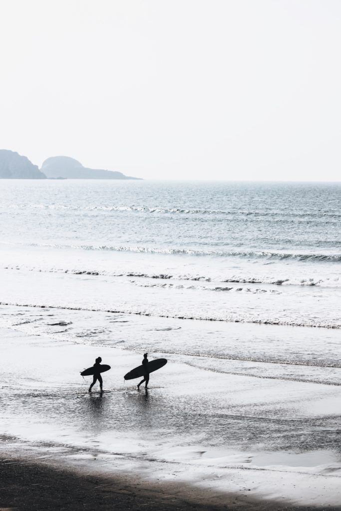 Image of two surfers walking into the ocean